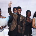 Danai Gurira, Chadwick Boseman, Isaach de Bankolé, Chadwick Boseman, Lupita Nyong'o and Angela Bassett. Black women in light blue and black dresses stand with Black men in black and brown suits behind black microphone and stand and in front of grey screen
