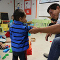 Man wearing gray sweatshirt sits in chair while holding arm of small child wearing blue and black striped sweater. Migrant families rest at the Catholic Charities Humanitarian Respite Center in McAllen, Texas on  June 21, 2018.