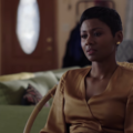 Emayatzy Corinealdi. Black woman in brown dress sits in brown chair in front of green sofa and brown walls and door