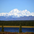 Mountain with white snow-capped peaks behind brown foothills and green trees and blue lake and in front of blue sky
