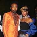 Donald Glover and Janelle Monáe. Black woman in gold crown and black dress poses next to Black man in black and orange suit in front of black wall and near other Black men in black and white attire