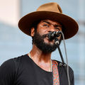 Gary Clark Jr. Black man with black beard in brown hat and black shirt sings into black microphone with brown guitar strap on shoulder in front of blue and white screen