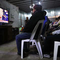 Migrants view a live televised speech by President Donald Trump on border security at a shelter for migrants in Tijuana, Mexico on January 8, 2019.