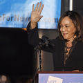 Kamala Harris. Black woman with brown hair in Black outfit smiles and waves in front of black wall with blue and white screen with black text and beige wall and behind podium with blue sign
