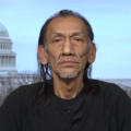 Nathan Phillips. Native American man with dark shoulder-length hair, wearing black shirt, with blue sky and Capitol Building in the background