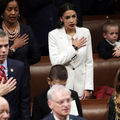 Alexandria Ocasio-Cortez. Latinx woman in white suit jacket with right hand over her heart, surrounded by other people and brown leather seating