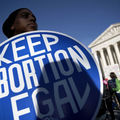 "Black pesron holds blue and white sign the reads, ""Keep abortion legal."""