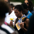 Black woman cries while holding yellow flower and yellow and blue funeral program while wearing black dress in crowd of Black families in black and white clothing