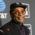 """Spike Lee. Black man in black hat and black and red glasses and suit smiles in front of grey wall with light grey images and blue logo and white text spelling """"AT&T"""""""