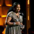 Tarana Burke. Black woman with black hair in gold and silver dress holds glass awards statue and speaks into black microphone in front of black and orange background