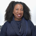 "Tarana Burke. Black woman with black hair smiles in navy sweater in front of white wall with black text that reads ""HBO"""