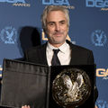 Alfonso Cuarón. Latinx man poses with gold and black award in black and white tuxedo in front of blue wall with blue and yellow icons
