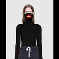 A White model wears a black sweater that comes over her mouth, surrounding it with red lips.