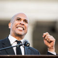 Cory Booker. Black man in white shirt and black suit and tie talks at podium