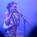 Jamila Woods. Black woman with black dredlocs in white tank top and blue denim shorts sings into black microphone on black stand in front of blue lights.