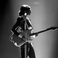 Janelle Monáe. Black-and-white image of Black woman in black and white performance attire playing white guitar behind black-and-white microphone stand in front of white lights.
