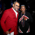 Jordan Peele and Spike Lee. Black man in red blazer and white shirt and pants poses next to Black man in black hat and red and black jacket in front of darkly lit background.