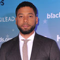 "Jussie Smollett. Black man in grey suit with light purple tie in front of purple and blue wall with white text that reads ""blackaids."""
