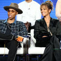 Lena Waithe and Halle Berry. Black woman in brown hat and black pants and shirt and navy and white flannel shirt sits on white chair next to Black woman in black pantsuit in White chair in front of Black man and woman and blue screen.