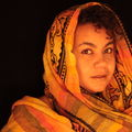 Black woman staring off with hair wrapped under a scarf in a dark background and orange tinted lighting
