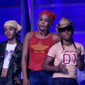 "Lisa ""Left Eye"" Lopes, T-Boz and Chilli of TLC. Black woman in yellow bandana and camouflage jacket next to Black woman in red bandana and shirt next to Black woman in coral shirt and brown hat in front of blue screen."