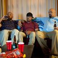 Three men of color sit side by side on a sofa looking as if watching something on television with beer bottles and a bag of chips in front of them on a coffee table.