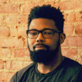 Damon Young. A head shot of a bearded Black man in black glasses with a black t-shirt smiling in front of a brick wall.