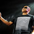 Black man with tight short hair stands onstage with black t-shirt and microphone and black sunglasses looking slightly left with head slightly tilted back in a break from performing.