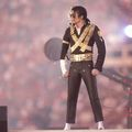 Performer Michael Jackson with curly hair in low ponytail wearing sunglasses and a gold studded black shirt and black pants standing on stage at a concert
