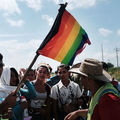 Photo of person holding a large rainbow flag stands with a small group of migrant travelers as they wait for a ride in Juchitan de Zaragoza, Mexico, on November 1, 2018.