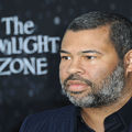 "A Black man with a salt and pepper view is turned to the side in front of a black background with a blue sign that reads ""The Twilight Zone "" behind him."