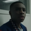 Black boy in blue, white and red jacket looks shocked