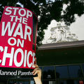 hands holding a sign that reads stop the war on choice