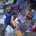 A small child wearing a blue hoodie sweatshirt pushes a purple stroller over a yellow street curb outside a closed temporary migrant shelter in Tijuana, Mexico on December 6, 2018.