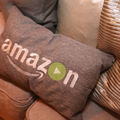 """A gold pillow that reads """"Amazon,"""" on a couch with other similarly hued  pillows around."""