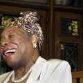 A Black woman turned to the side laughs while wearing a hat