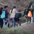 A group of migrant women and children walk past a U.S. Border Patrol agent after crossing over the U.S.-Mexico border fence in Tijuana, Mexico on December 2, 2018.