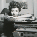 Lorraine Hansberry. Black-and-white image of Black woman in checkered shirt leaning on typewriter in front of lamp and artwork on walls