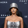 "Rihanna. A Black woman stands against a black wall that reads ""Sephora"" in white letters, while wearing a gray and black snakeprint dress and matching hat."