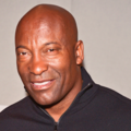 John Singleton. Bald Black man in black zip-fleece.