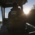 Border Patrol stands and rides small boat near U.S. Mexico border> His back is to the camera and the back of his jacket reads, Border Patrol.