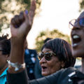 Three black women two of whom are wearing sunglasses one of whom is wearing glasses cheer at a rally