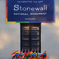 Stonewall Inn with pride flags and plaque showing memorial.
