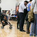 Baby in stroller waits as midterm election voters cast their ballots at Atlanta, Georgia's Grady High School polling station on November 6, 2018.
