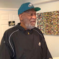 Bill Cosby. Older Black man with gray beard, wearing green cap and black top.