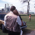 A Black man holds a Black boy standing in front of chemical plants