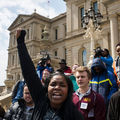Protesters shout and raise fists outside a Flint, Michigan, municipal building.