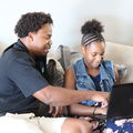 Black man in dark shit sits on couch with teen daughter as they work on a black laptop