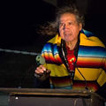 Frank LaMere. Older Native American man in yellow, blue and red-stripes at podium with long gray hair blowing.