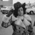 Linda Taylor. Black woman in a black and white photo, wearing a fur coat with her hand on her hat walking in parking lot in Chicago.
